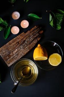 Чашка зеленого чая, ароматическая палочка, свечи и лимоны на черном столе