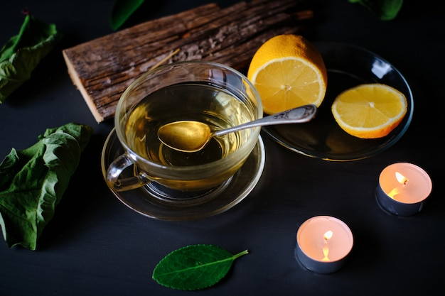 Green tea cup, incense stick, candles and lemons on black table