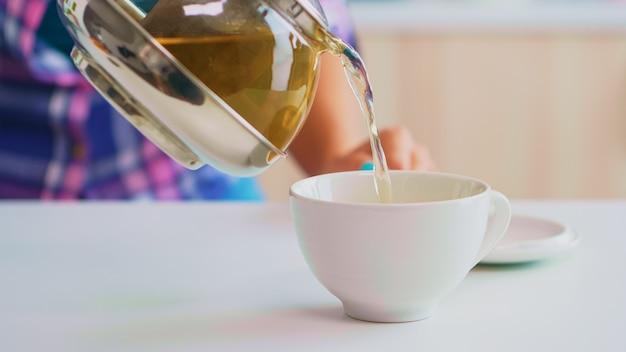 急須からスローモーションで流れる緑茶。やかんからお茶のクローズアップは、ティーカップと健康的なハーブの葉を使用して、朝食時にキッチンの磁器カップにゆっくりと注ぎます。