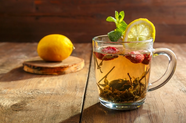 Green tea in a glass cup with strawberries mint and lemon on a wooden table. horizontal photo