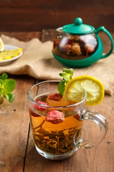 Green tea in a glass cup with strawberries mint and lemon on a wooden table and a teapot and lemon in a plate and mint leaves.