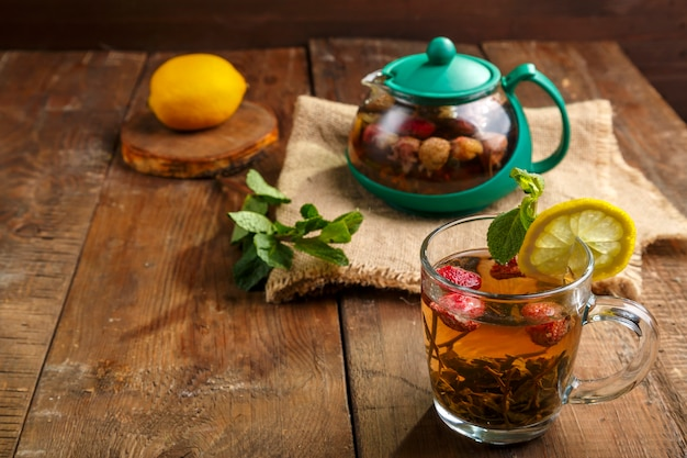 Green tea in a glass cup with strawberries mint and lemon on a wooden table and a teapot and lemon in a plate and mint leaves