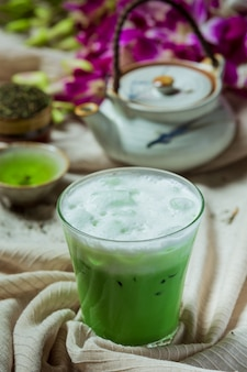 Green tea iced in a tall glass with cream topped with iced green tea. decorated with green tea powder.