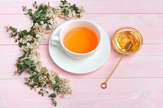 Зеленый чай в керамической чашке с ветвями цветущих веток деревьев