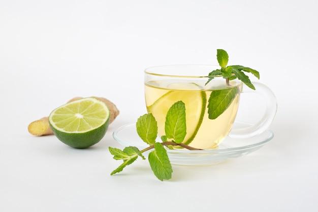 ガラスのカップに緑茶、白いテーブルに生姜、ライム、ミント。健康食品