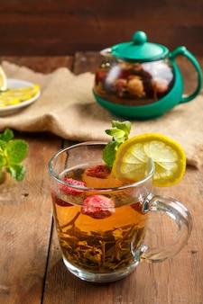 ガラスのカップに入った緑茶と、木製のテーブルにイチゴのミントとレモン、皿にティーポットとレモン、ミントの葉。