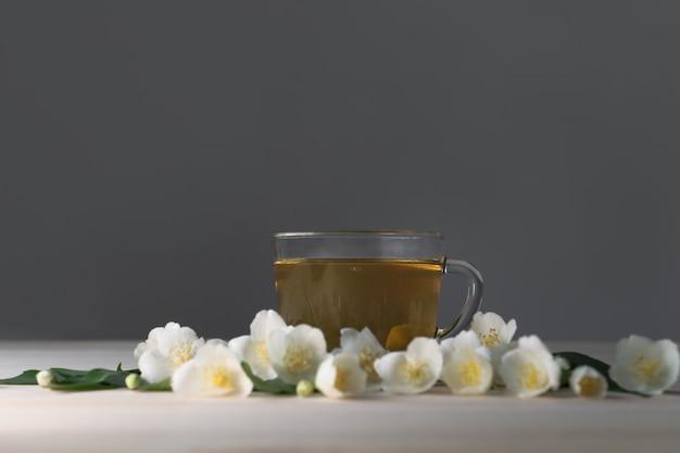 Зеленый чай в стеклянной прозрачной чашке с белыми цветами жасмина на сером фоне стены