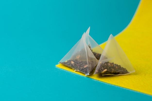 Зеленый чай в мешке-пирамиде на желто-синем фоне. копировать пространство
