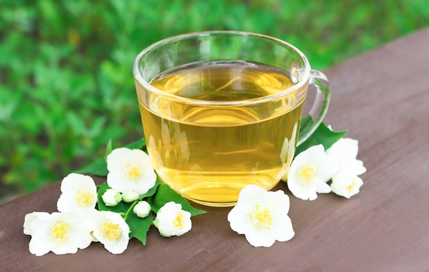 Зеленый чай в прозрачной стеклянной чашке на столе в саду