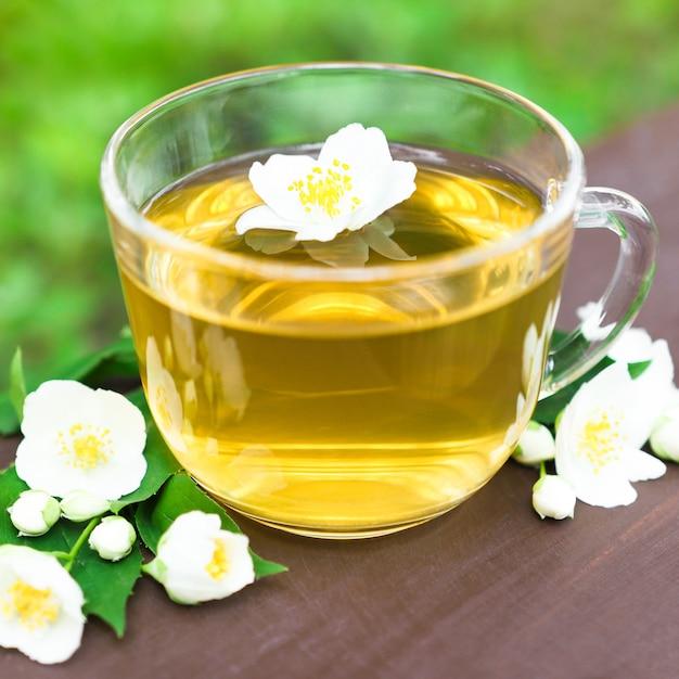Зеленый чай в прозрачной стеклянной чашке с белыми цветами жасмина и ветвями на деревянном столе крупным планом