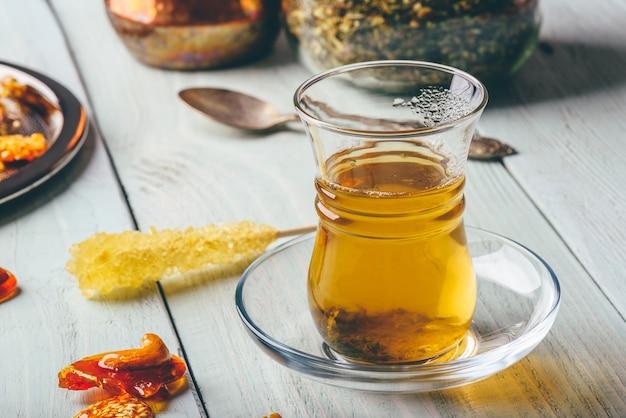 Зеленый чай в бокале армуду с восточными ореховыми лакомствами на металлической тарелке на светлой деревянной поверхности