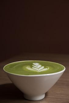 Зеленый чай латте в белом керамической чашке на деревянный стол с коричневым фоном Premium Фотографии