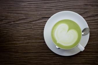 Green tea latte on wood background