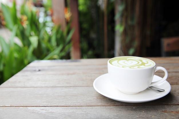 Латте зеленый чай на фоне дерева
