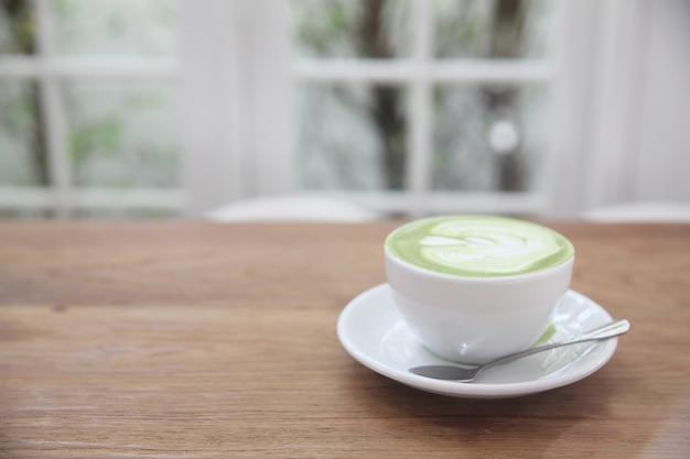 木の背景に緑茶ラテ