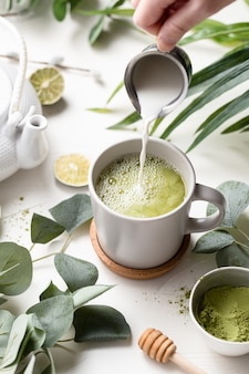 Green tea latte with milk in a white cup with green leaves and wooden spoon