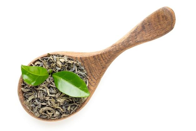 Листья зеленого чая ложкой, изолированные на белом фоне
