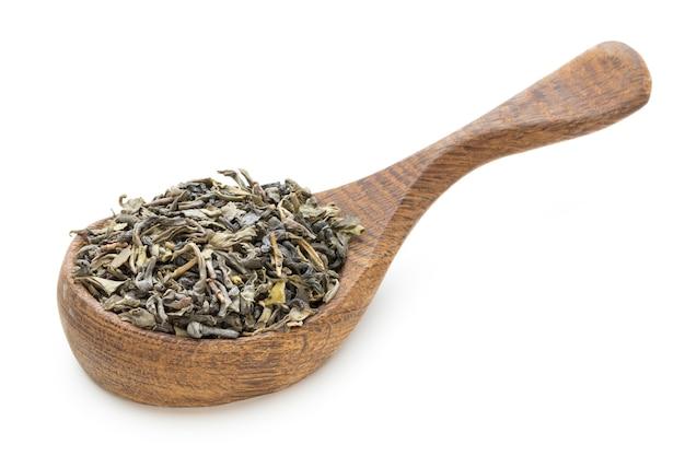 Листья зеленого чая изолированные ложкой изолированной на белизне.