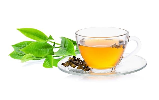 白い背景の上のお茶のガラスと緑茶の葉