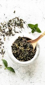緑茶はミントで生い茂った白い大理石のボウルに背景を残します
