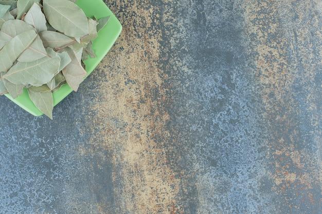 Foglie di tè verde sul piatto verde.