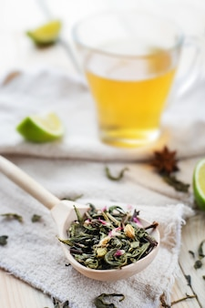 ライムスライスと淹れたてのお茶のマグカップ、クローズアップとリネン織物の上の木のスプーンで緑茶の葉