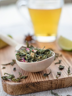 Green tea leaves in wooden spoon with lime slices and mug of brewed tea on wooden background or surface, close-up