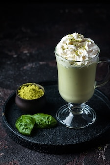 Green tea matcha latte in a glass cup on black background concept of a healthy diet superfood antioxidant cleansing