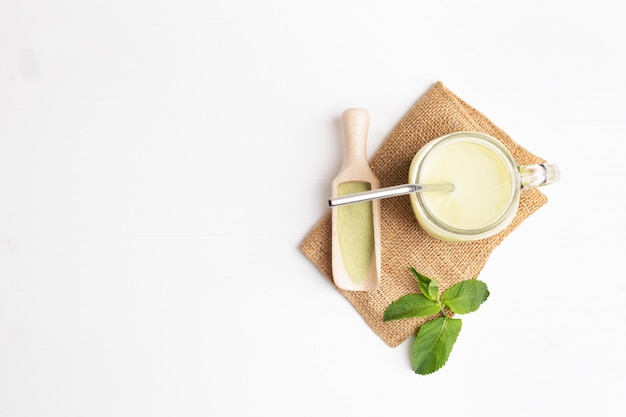 Green tea matcha latte in glass jar with metal drinking straw and mint and spice spatula on sackcloth. top view with copy space