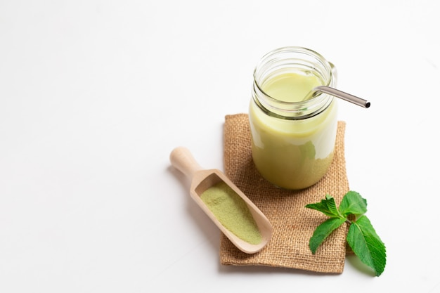 Green tea matcha latte in glass jar with metal drinking straw and mint and spice spatula on sackcloth