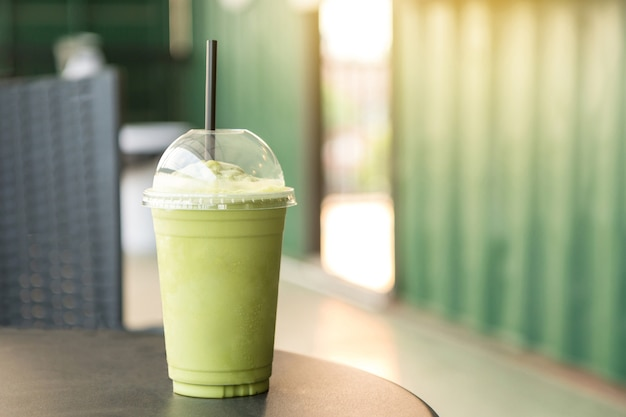 Green tea matcha smoothies in plastic cup in the coffee shop