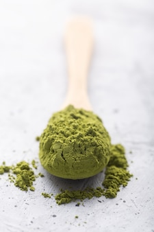 Green tea matcha in a spoon on concrete surface. close up shot