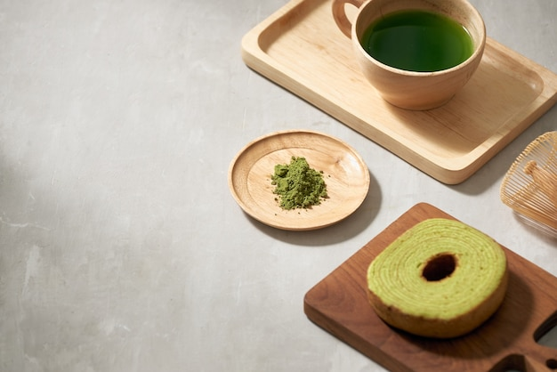 Green tea matcha in a wooden cup with german cake on the brown mat close-up