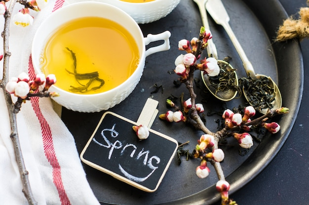 Green tea and peach blossom as a spring concept with copy space