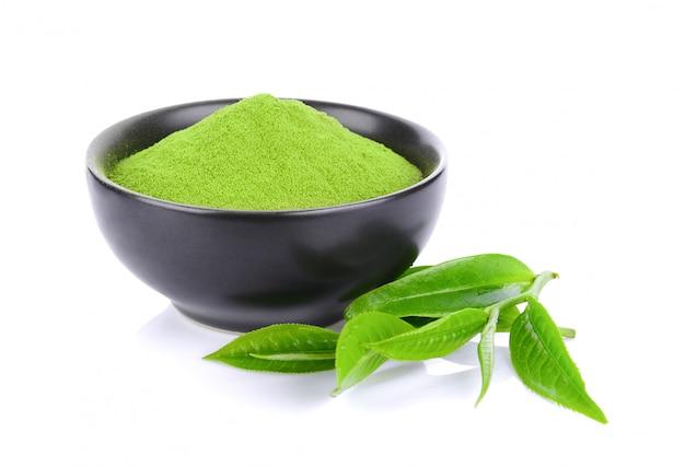 Порошок и листья зеленого чая изолированные на пустом пространстве