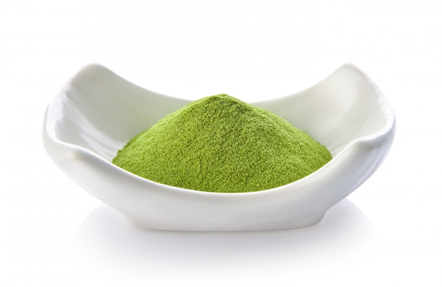 Green tea powder in a bowl on white space