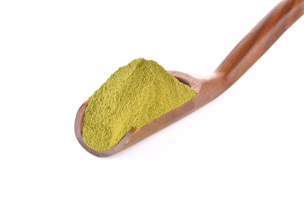 Порошок зеленого чая в деревянной ложке на белом