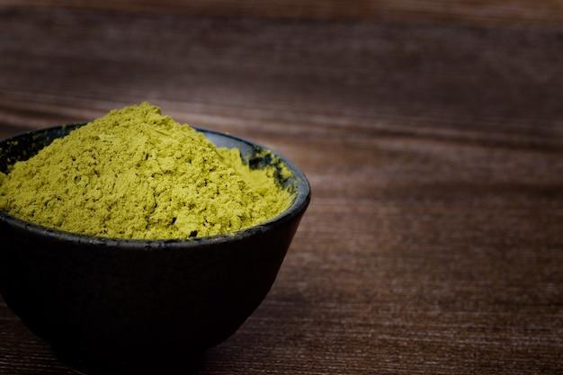 Порошок зеленого чая в миске на деревянном