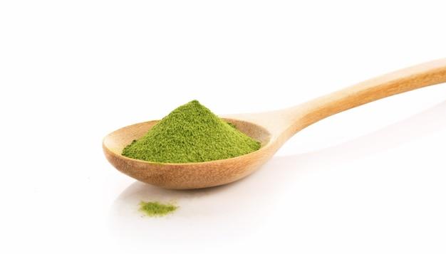 Порошок зеленого чая в ложке, изолированные на белом фоне