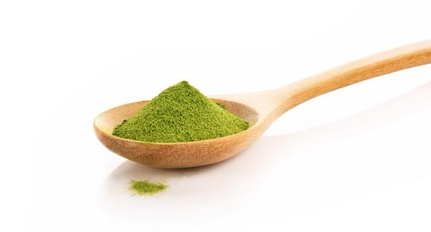 Порошок зеленого чая в ложке изолированные