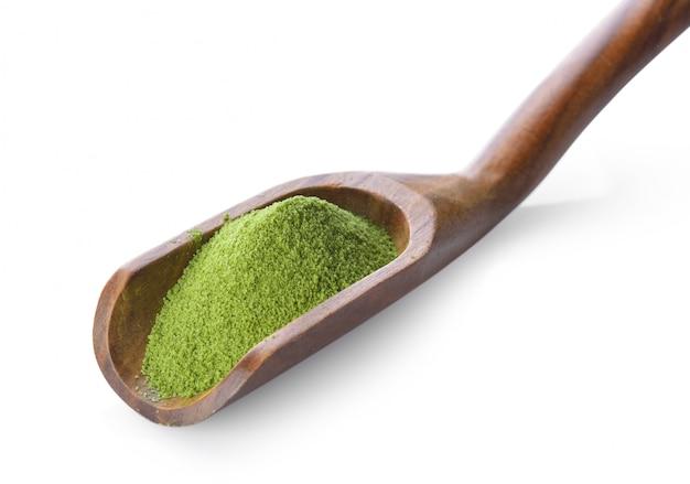 Порошок зеленого чая в ложке на белом пространстве