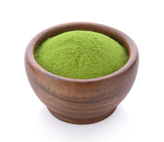 Порошок зеленого чая в деревянной миске на белом пространстве