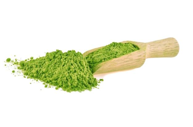 白い背景で隔離の木製スクープの緑茶粉末