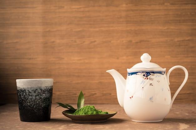 Зеленый чай с керамической чашкой и чайником на деревянном фоне.