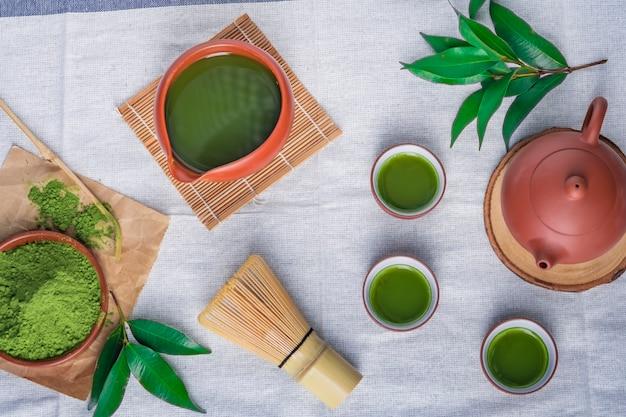Порошок зеленого чая с листиком в керамическом блюде на столе, венчик из японской проволоки из бамбука для чайной церемонии матча Premium Фотографии