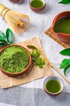 Порошок зеленого чая с листиком в керамическом блюде на столе, венчик из японской проволоки из бамбука для чайной церемонии матча
