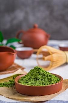 Порошок зеленого чая с листиком в керамическом блюде на столе, японская проволока венчик из бамбука