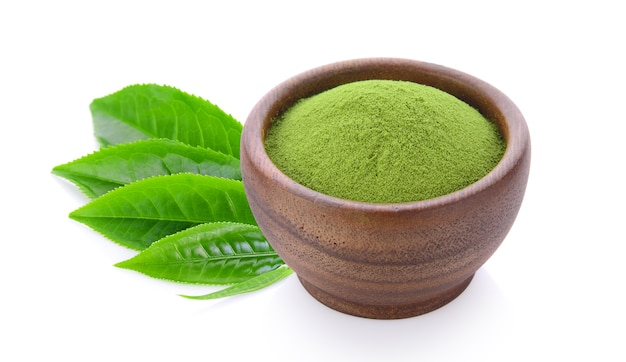 Green tea powder in wood bowl on white surface