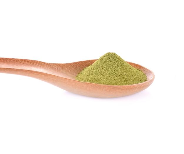 Деревянная ложка порошка зеленого чая на белом фоне