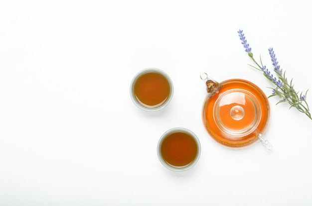 Green tea in a transparent teapot and small cups on a white table.